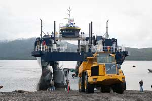 A dump truck rolls from the vechicle deck of the M/V Susitna directly onto the beach